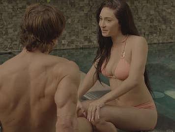Joven modelo en bikini folla con su novio en la piscina