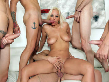 The exuberant busty blond Argentine slut, Blondie Fesser in a bukkake scene, with 7 cocks fucking her mouth and her pussy