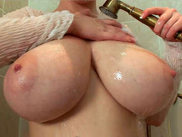 Curvy blonde with huge natural tits rubs her shaved pussy in the shower
