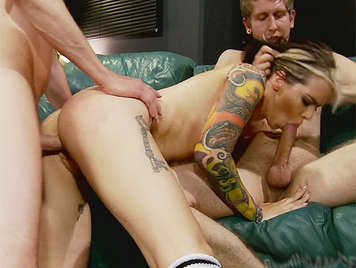 Horny tattooed blonde fucked by two huge cocks that fills the mouth with a torrent of hot cum