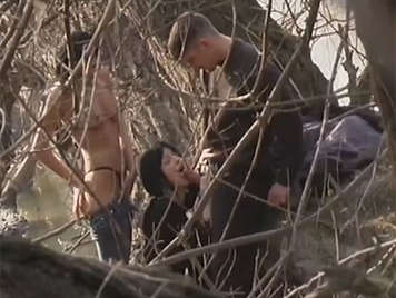 Two girls and a guy fucking in the forest are observed by a voyeur