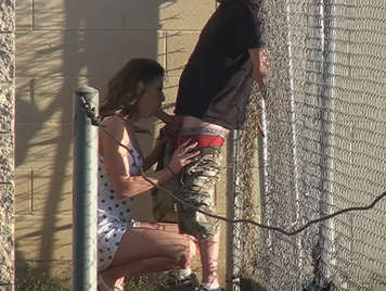 Couple fucking in public next to a fence in the middle of the street