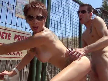 A busty mom is fucked in front another couple in a public area for nudists