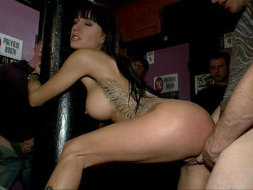 Fucking a slut brunette with operated tits tied to the column of a bar