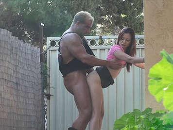 Asiatica y gigante musculoso follando en publico junto a un lateral de una casa