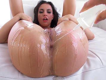 Young brunette slut covered in oil in  anal scene