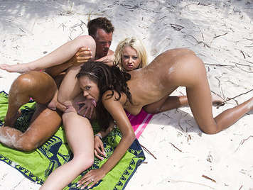 Two babes fucked hard by their asses in the beach